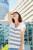 Смеясь над более старая женщина с рукой в волосах стоя в городе Стоковое Изображение RF
