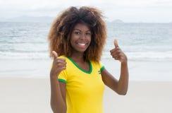 Смеясь над бразильская девушка при шальной стиль причёсок показывая оба большого пальца руки вверх Стоковая Фотография