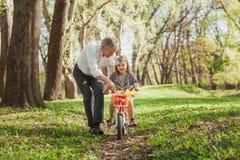 Смеясь над велосипед катания девушки с дедом Стоковые Фото
