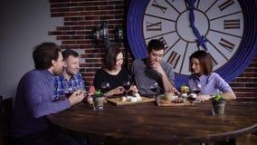 Смеясь над группа людей имея обедающий совместно акции видеоматериалы