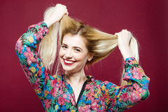 Смеясь над девушка при длинные волосы нося красочную рубашку имеет потеху в студии Молодая женщина с очаровательной улыбкой на пи Стоковые Фото