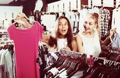 2 смеясь над девушки выбирая платье совместно Стоковое Изображение RF