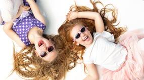 2 смеясь над девушки лежа на белом поле Стоковые Изображения