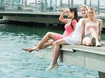 3 смеясь над девушки сидя на пристани в городке Стоковое Изображение