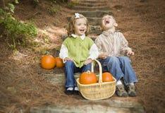 Смеясь над дети брата и сестры сидя на деревянных шагах с тыквами Стоковое фото RF