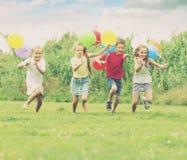 4 смеясь над дет бежать на зеленой лужайке Стоковая Фотография