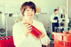 Смеясь над женские бутылки вина упаковки работника Стоковые Фотографии RF