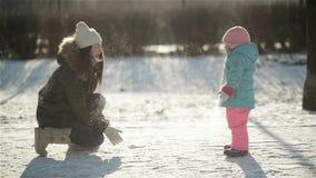 Смеясь над женщина в теплой одежде бросает снег на ее Snowsuit дочери нося Мать и ребенок наслаждаясь холодное солнечным сток-видео