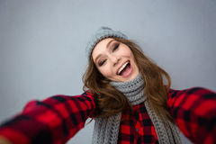 Смеясь над женщина в шляпе и шарфе делая фото selfie Стоковое фото RF