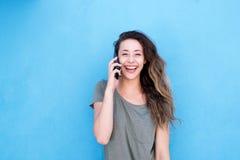 Смеясь над женщина говоря на мобильном телефоне против голубой предпосылки Стоковые Фото