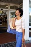 Смеясь над женщина держа хозяйственные сумки вне мола Стоковое Изображение RF