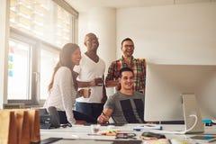 Смеясь над женщина и люди на компьютере в офисе Стоковое Изображение