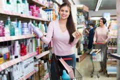 Смеясь над женщина стоя с магазинной тележкаой Стоковые Фото