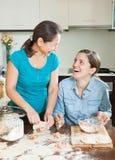 Смеясь над женщины делая пироги или вареники мяса Стоковые Изображения