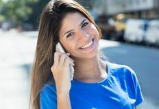 Смеясь над кавказская женщина в голубой рубашке на телефоне Стоковое Фото