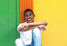 Смеясь над карибский парень сидя перед красочной стеной стоковые фото