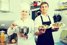 Смеясь над кашевар женщины давая салат к официантке Стоковые Фото