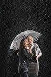Смеясь над коммерсантки под одним зонтиком в дожде Стоковые Фотографии RF