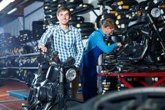 Смеясь над клиент человека держа его мотоцикл Стоковая Фотография