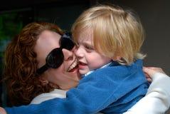 Смеясь над мать обнимает ребенка стоковое изображение rf