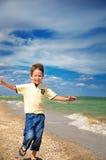 Смеясь над мальчик бежит к и настроил оружия к стороне стоковые фото