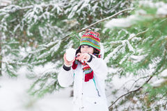 Смеясь над мальчик играя шарик снега воюет в снежной передней части Стоковые Изображения RF