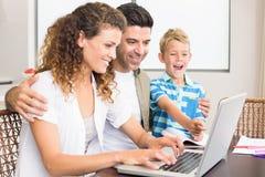 Смеясь над мальчик используя компьтер-книжку с родителями на таблице Стоковые Фотографии RF