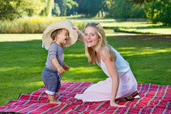 Смеясь над мальчик пробуя на шляпе с матерью снаружи Стоковые Фото