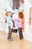 Смеясь над милые мальчик и девушка выбирают одежды совместно Стоковое Изображение