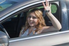 Смеясь над молодая женщина водителя сидит в автомобиле Стоковое Изображение RF