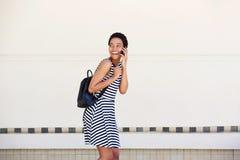 Смеясь над молодая женщина идя и говоря на мобильном телефоне Стоковые Изображения