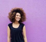 Смеясь над молодая женщина стоя против фиолетовой предпосылки Стоковое Изображение RF