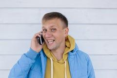 Смеясь над молодой человек говоря на телефоне использование телефона человека франтовское Стоковая Фотография