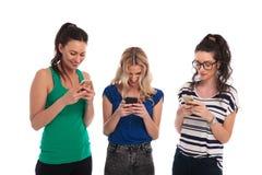 Смеясь над молодые женщины читая текстовые сообщения на их телефонах Стоковое Изображение RF