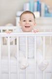 Смеясь над младенец в младенце кроватки дома - в кровати Стоковое фото RF