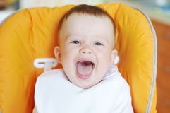Смеясь над младенец в bib сидит на стуле младенца Стоковая Фотография RF