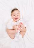 Смеясь над младенец лежит на кровати стоковые изображения rf