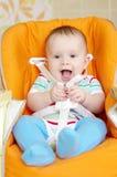 Смеясь над младенец сидя на младенцах предводительствует время 6 месяцев стоковые фото