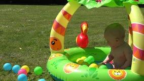 Смеясь над младенческий младенец брызгает воду в бассейне вполне красочных шариков 4K акции видеоматериалы