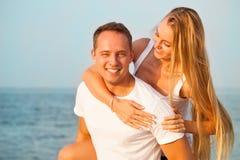 Смеясь над пары наслаждаясь природой над предпосылкой моря привлекательностей стоковая фотография