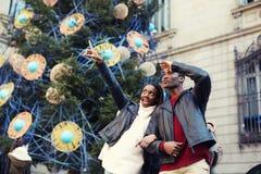 Смеясь над пары на каникулах рождества идя в город Стоковая Фотография