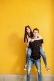 Смеясь над пары подростка на желтой стене Стоковые Изображения RF