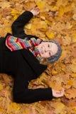 Смеясь над падение листьев женщины лежа Стоковая Фотография RF
