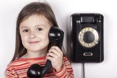 Смеясь над ребенок говоря на телефоне, белой предпосылке Стоковое Изображение