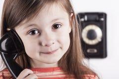 Смеясь над ребенок говоря на телефоне, белой предпосылке Стоковые Фото