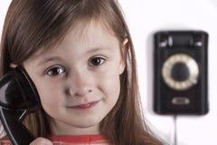 Смеясь над ребенок говоря на телефоне, белой предпосылке Стоковое фото RF