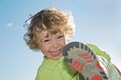Смеясь над ребенок играя outdoors Стоковые Изображения