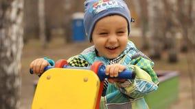 Смеясь над ребенок тряся на коромысле в парке сток-видео