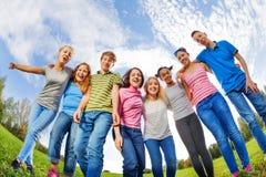 Смеясь над друзья разнообразия стоят на траве в строке Стоковое Изображение RF