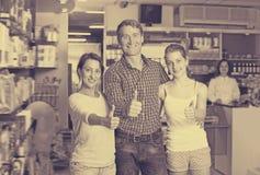 Смеясь над семья из трех человек держа большие пальцы руки вверх Стоковые Фото